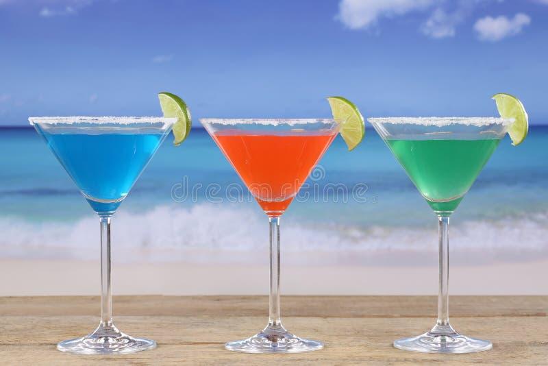 在马蒂尼鸡尾酒玻璃的五颜六色的鸡尾酒在海滩 图库摄影