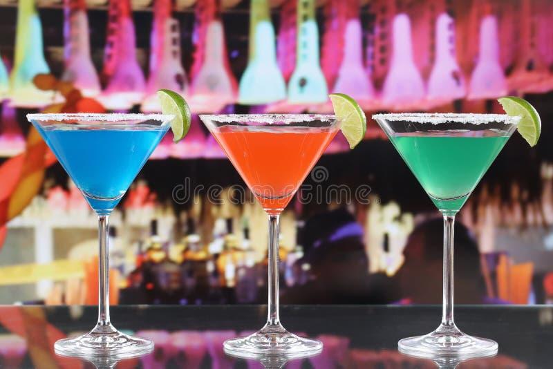 在马蒂尼鸡尾酒玻璃的五颜六色的鸡尾酒在酒吧 免版税图库摄影