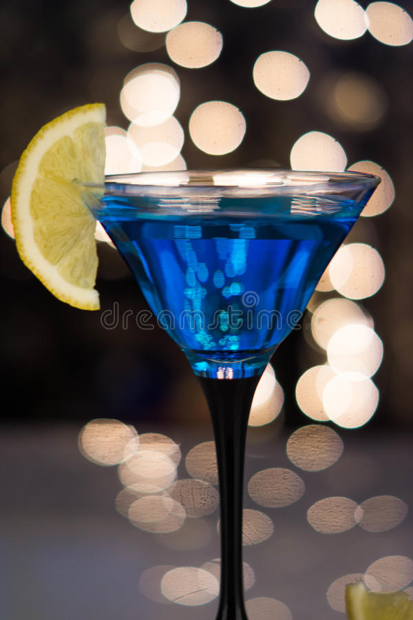 在马蒂尼鸡尾酒玻璃的蓝色鸡尾酒与切片柠檬 图库摄影
