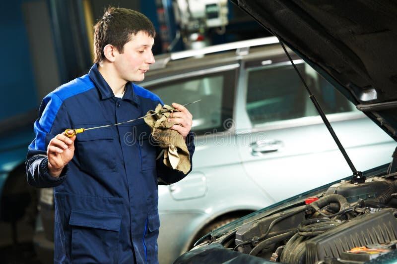 在马达引擎的汽车修理师审查的油 免版税库存照片