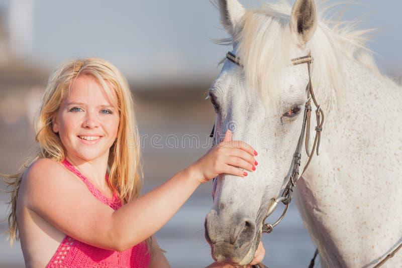 在马附近的年轻愉快的妇女 库存照片