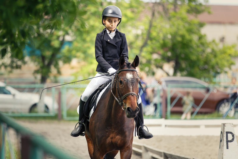 在驯马的幼小十几岁的女孩骑乘马 免版税库存图片