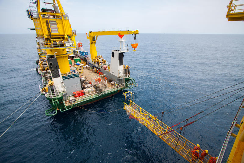 在驳船和油和煤气平台,工作者之间的通道走了通过工作的方式在平台 图库摄影