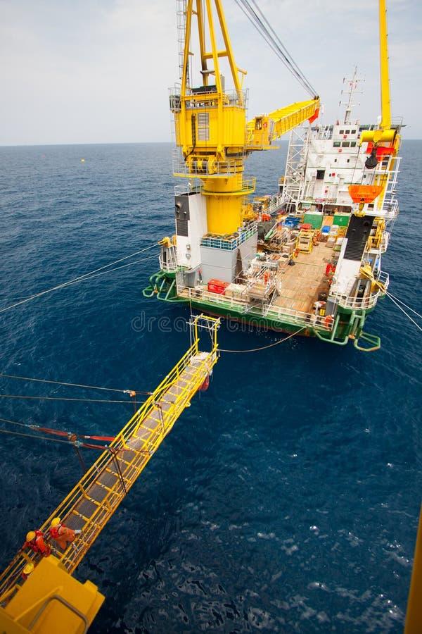 在驳船和油和煤气平台,工作者之间的通道走了通过工作的方式在平台 库存照片
