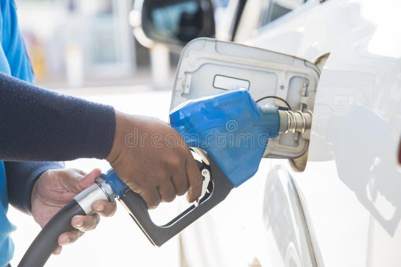 在驻地的充填气体 重新装满油,汽油,柴油车 重新装满有燃料的手汽车 库存图片