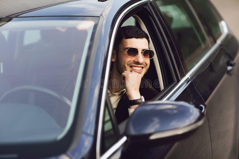 在驾驶他的汽车的衣服和黑玻璃的年轻bussinesman 企业神色 新的汽车的实验驾驶 图库摄影