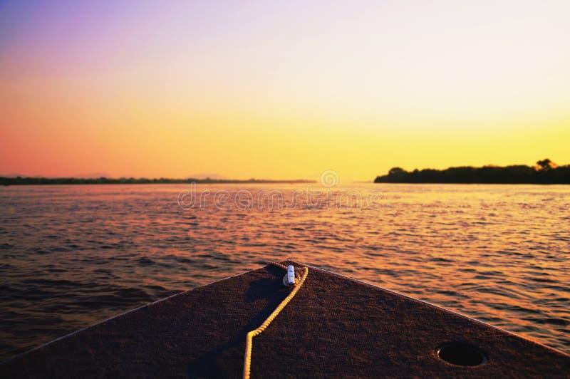在驾驶在平底锅的小船的日落的惊人的五颜六色的风景 免版税库存图片
