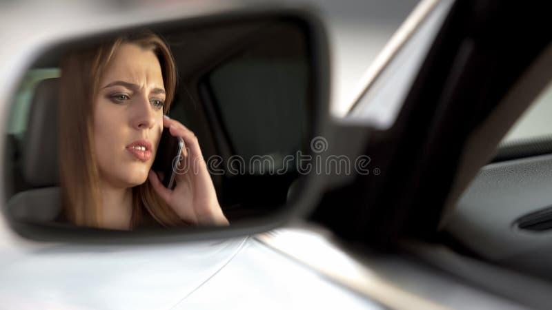 在驾驶席的年轻哀伤的女性开会和谈话与男朋友,终止 库存图片