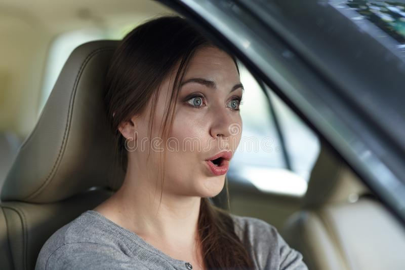 在驾驶有惊讶或震动,嘴鬼脸的轮子后的年轻可爱的白种人妇女一辆汽车打开了 库存图片