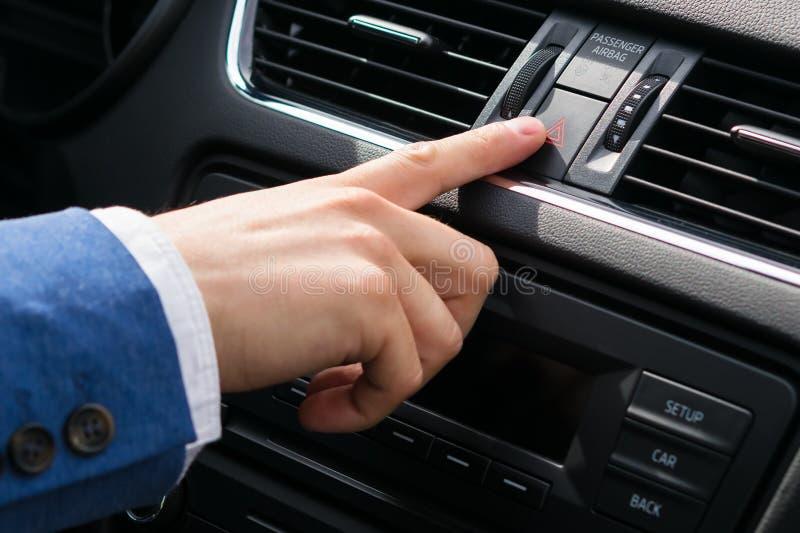 在驾驶期间,一只人的手的手指按应急照明按钮,防止危险 免版税库存照片