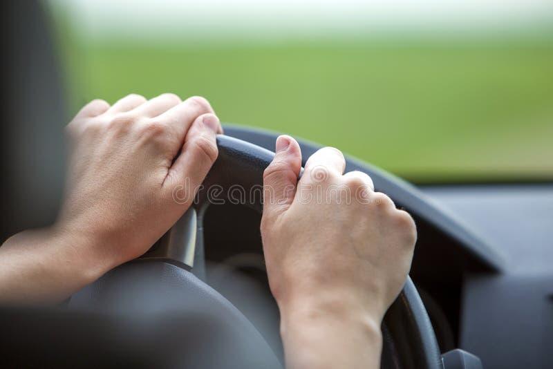 在驾驶汽车的方向盘的妇女手 免版税库存图片