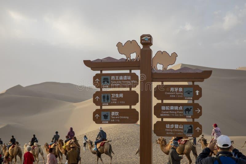 在骆驼的旅游标志乘坐,唱沙子山,塔克拉玛干沙漠 免版税图库摄影