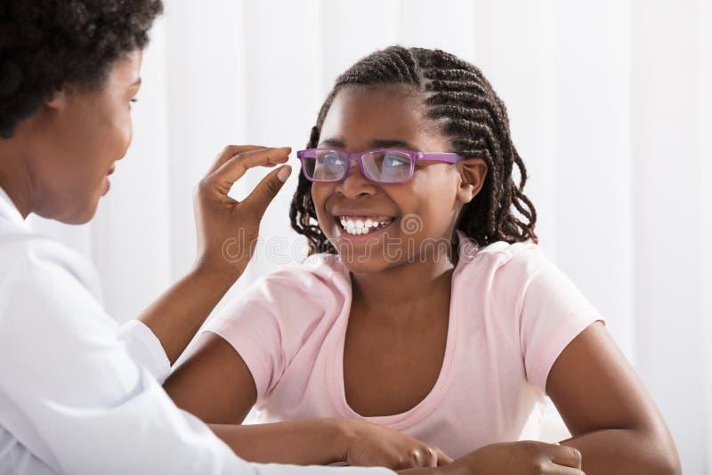 在验光师前面的微笑的女孩佩带的镜片 免版税库存图片