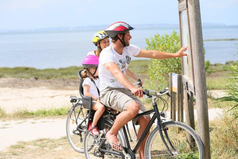 在骑自行车的旅途上的家庭由海 图库摄影