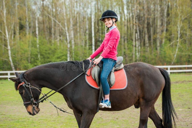 在骑马展示的幼小女运动员骑乘马跳竞争 十几岁的女孩乘驾马 库存照片