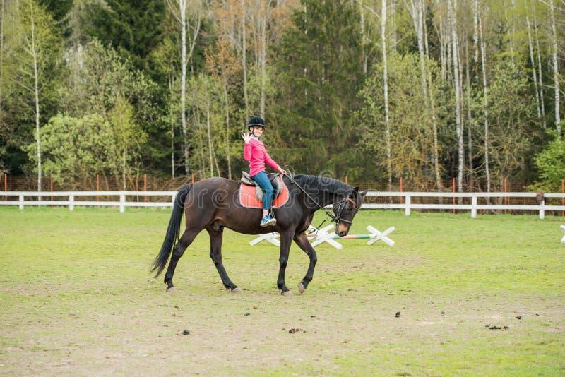 在骑马展示的幼小女运动员骑乘马跳竞争 十几岁的女孩乘驾马 免版税图库摄影