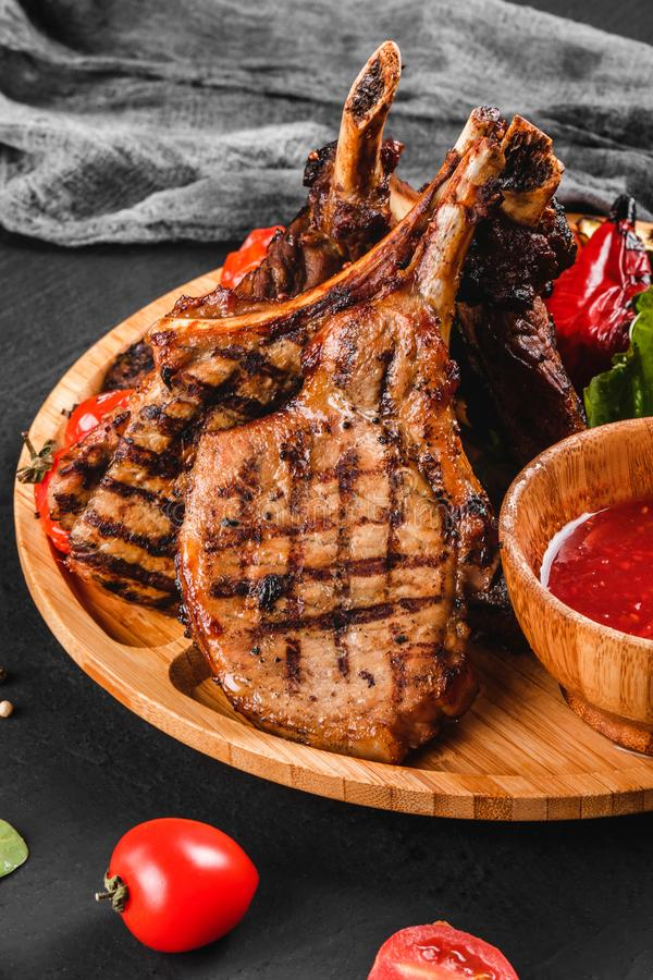 在骨头和菜的烤Ribeye牛排用新鲜的沙拉和bbq调味汁在切板在黑石背景 库存图片