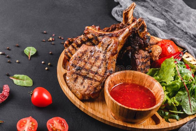在骨头和菜的烤Ribeye牛排用新鲜的沙拉和bbq调味汁在切板在黑石背景 ?? 免版税库存图片