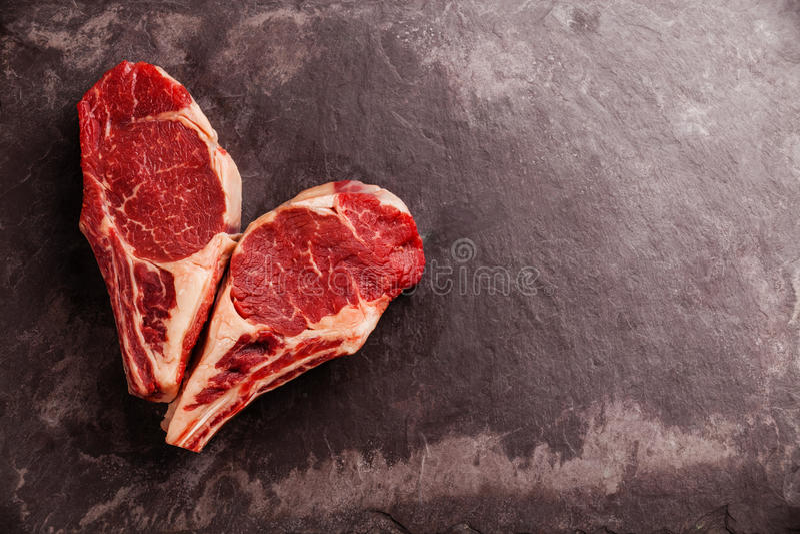 在骨头的心脏形状未加工的牛排 库存图片