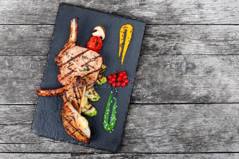 在骨头的烤猪肉牛排充塞用乳酪、烤菜和莓果在石板岩背景在木背景 库存照片