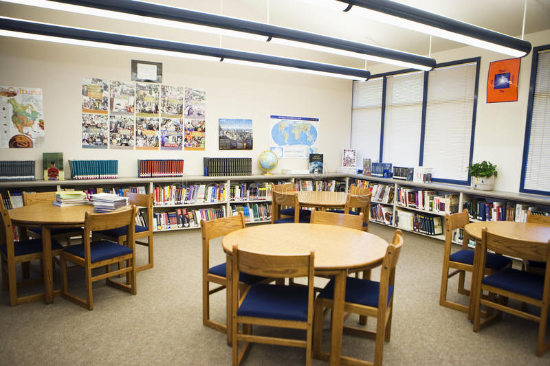 在高中图书馆里和椅子安排的表 免版税库存图片