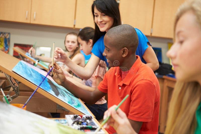 在高中艺术课的公学生与老师 免版税库存照片
