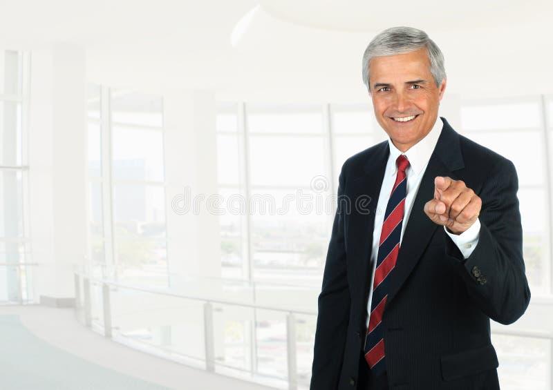在高关键办公室设置的成熟商人指向照相机的 库存图片