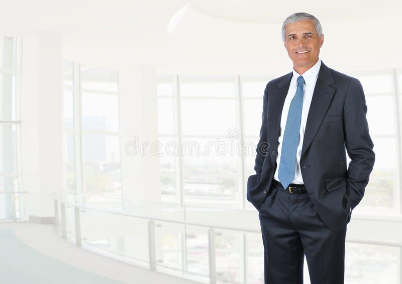 在高关键办公室设置,在口袋的手的一个成熟商人身分 免版税库存图片