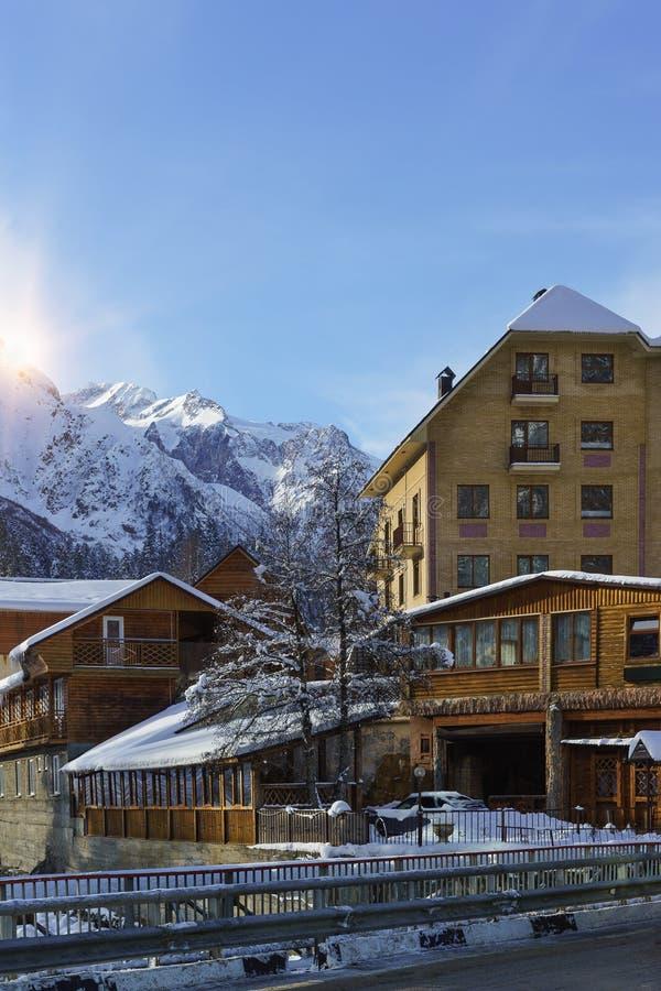 在高加索山脉的积雪覆盖的峰顶的太阳光芒 在滑雪场Dombay的冬天黎明 免版税库存图片