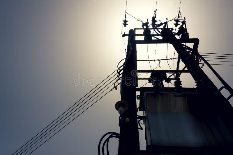 在高压塔下的太阳背后照明在背景中 免版税图库摄影