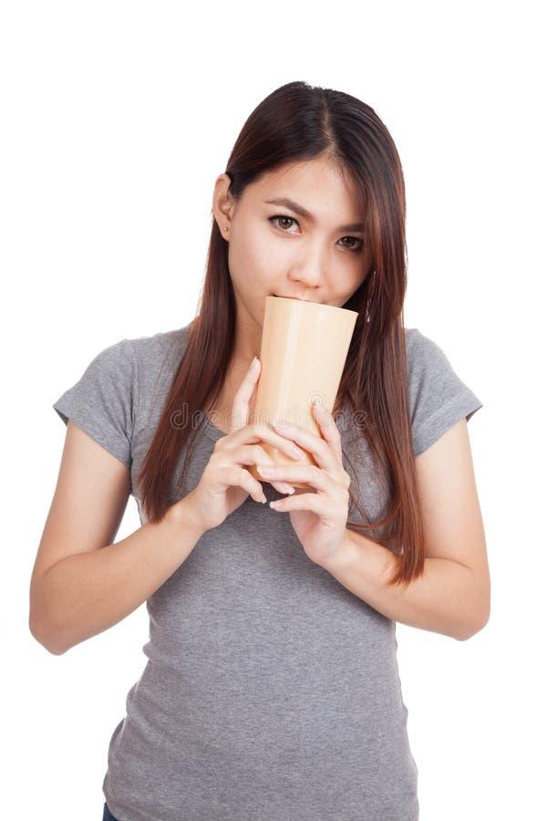 在高塑料玻璃的年轻亚洲妇女气味饮料 免版税库存照片