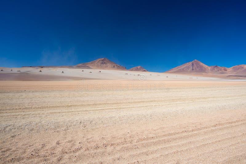 在高处的土路与含沙沙漠和贫瘠火山在安地斯山的高地排列 到著名Uyuni盐的旅行 免版税图库摄影