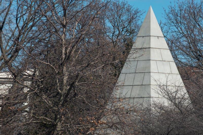 在高大的树木包围的公墓的大金字塔 免版税库存图片