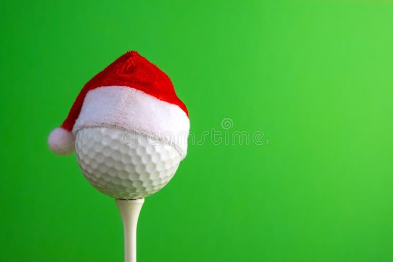 在高尔夫球、圣诞节和新年题目的体育概念  在一个红色圣诞老人项目帽子的白色高尔夫球在发球区域设置了 绿色 免版税图库摄影