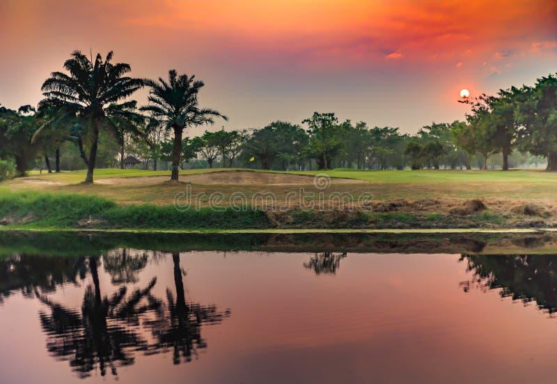 在高尔夫球场湖的日落 库存图片