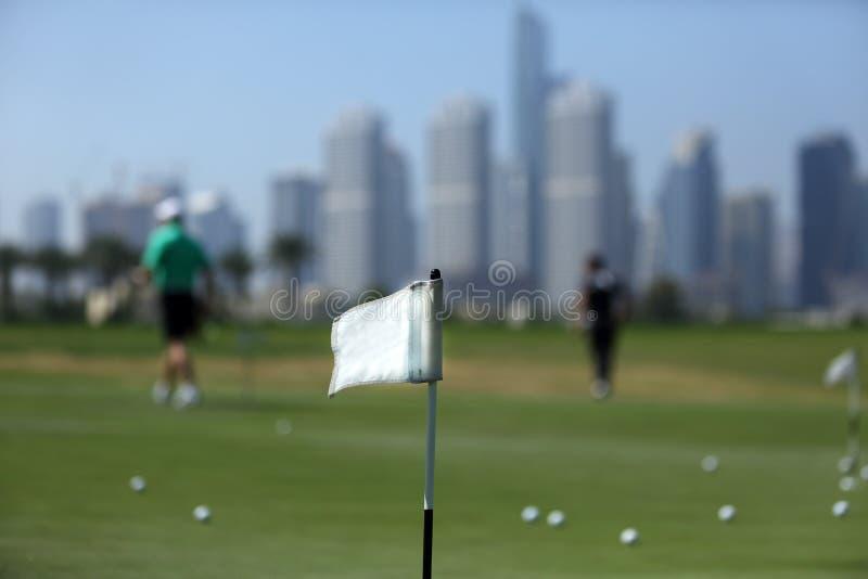 在高尔夫球场的一面旗子在高尔夫球运动员和摩天大楼中在迪拜 免版税库存照片