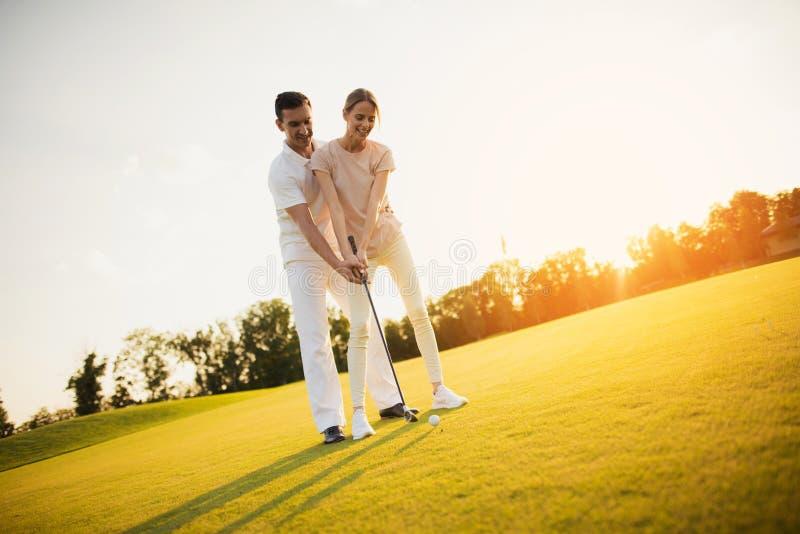 在高尔夫球场的浪漫日期 学会的夫妇打高尔夫球 库存照片