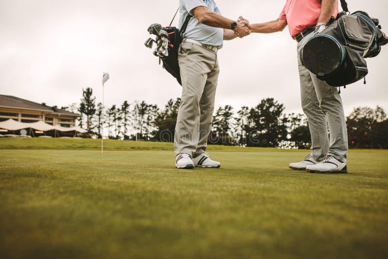 在高尔夫球场的资深高尔夫球运动员握手 图库摄影