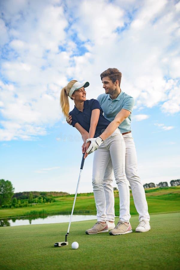 在高尔夫球场的年轻夫妇 图库摄影
