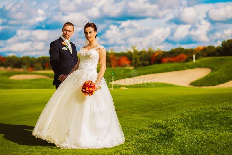 在高尔夫球领域的美好的愉快的已婚夫妇 库存图片