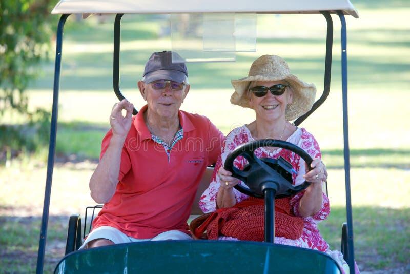 在高尔夫车的资深夫妇 库存图片