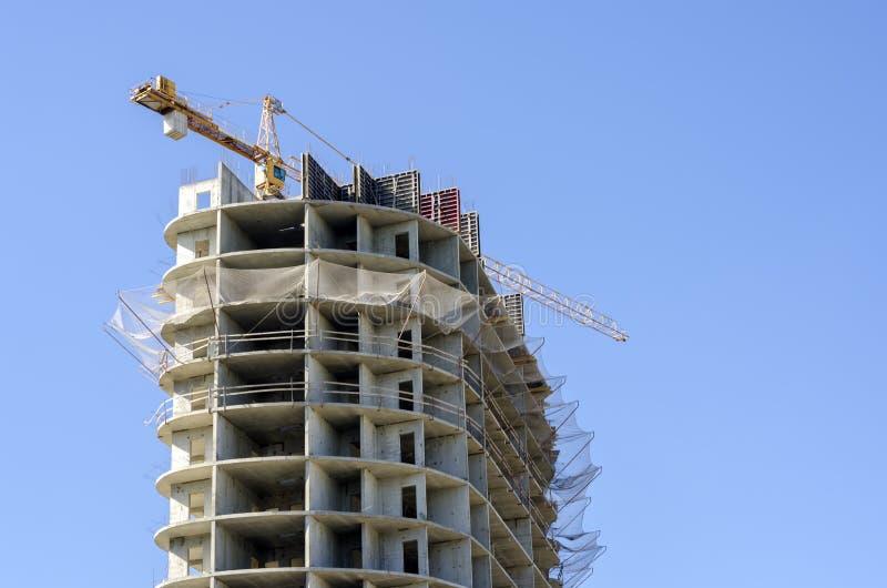 在高层建筑物建设中特写镜头的黄色起重机 免版税库存照片