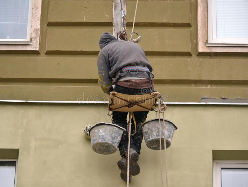 在高层的人工作运作金属,涂灰泥房子 库存照片