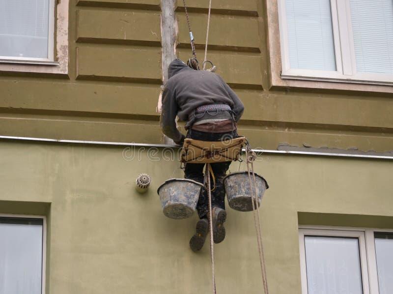 在高层的人工作运作金属,涂灰泥房子 免版税库存照片