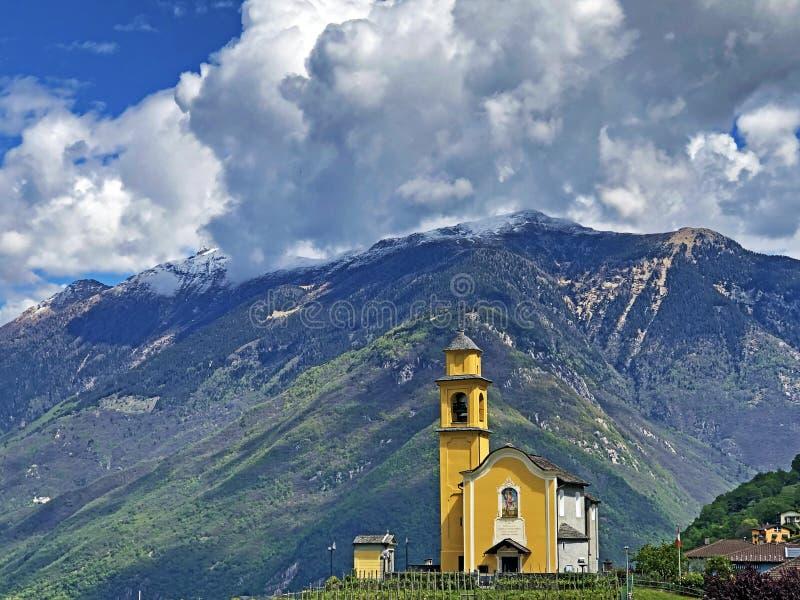 在高山峰顶和贝林佐纳镇的童话云彩 库存图片