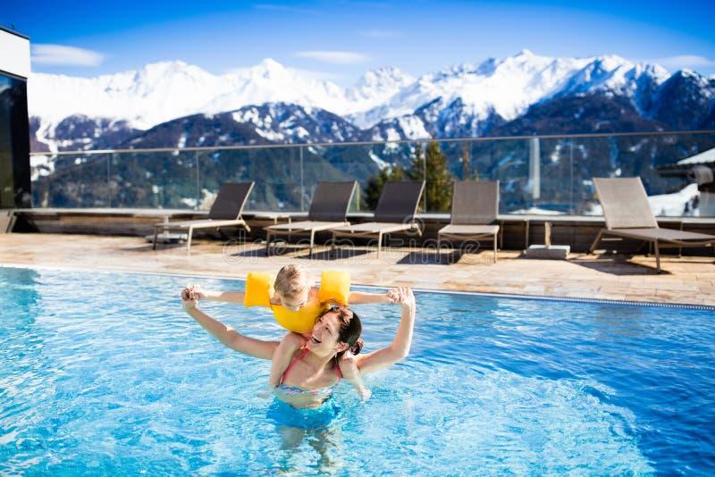 在高山温泉渡假胜地室外游泳池的家庭  库存图片