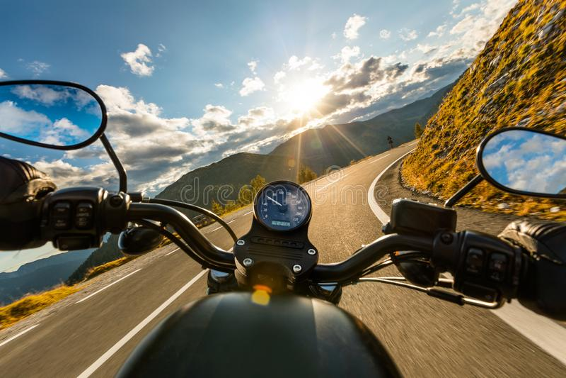 在高山高速公路的摩托车驾驶员骑马,把手视图,奥地利,欧洲 库存照片