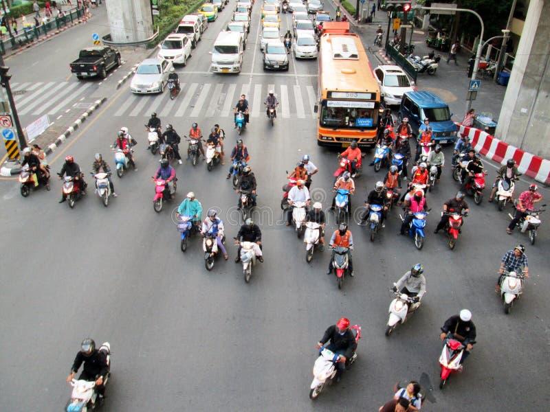 在高峰时间,摩托车骑士和汽车等待在连接点 免版税库存照片