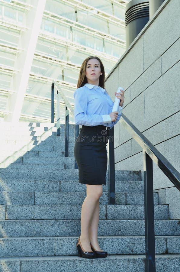在高建筑学附近的美好的年轻女商人身分在鞋子和短的黑裙子,调查距离 库存照片