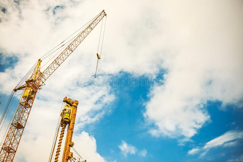 在高楼建设中和起重机的地方里面在天空蔚蓝下 免版税库存图片